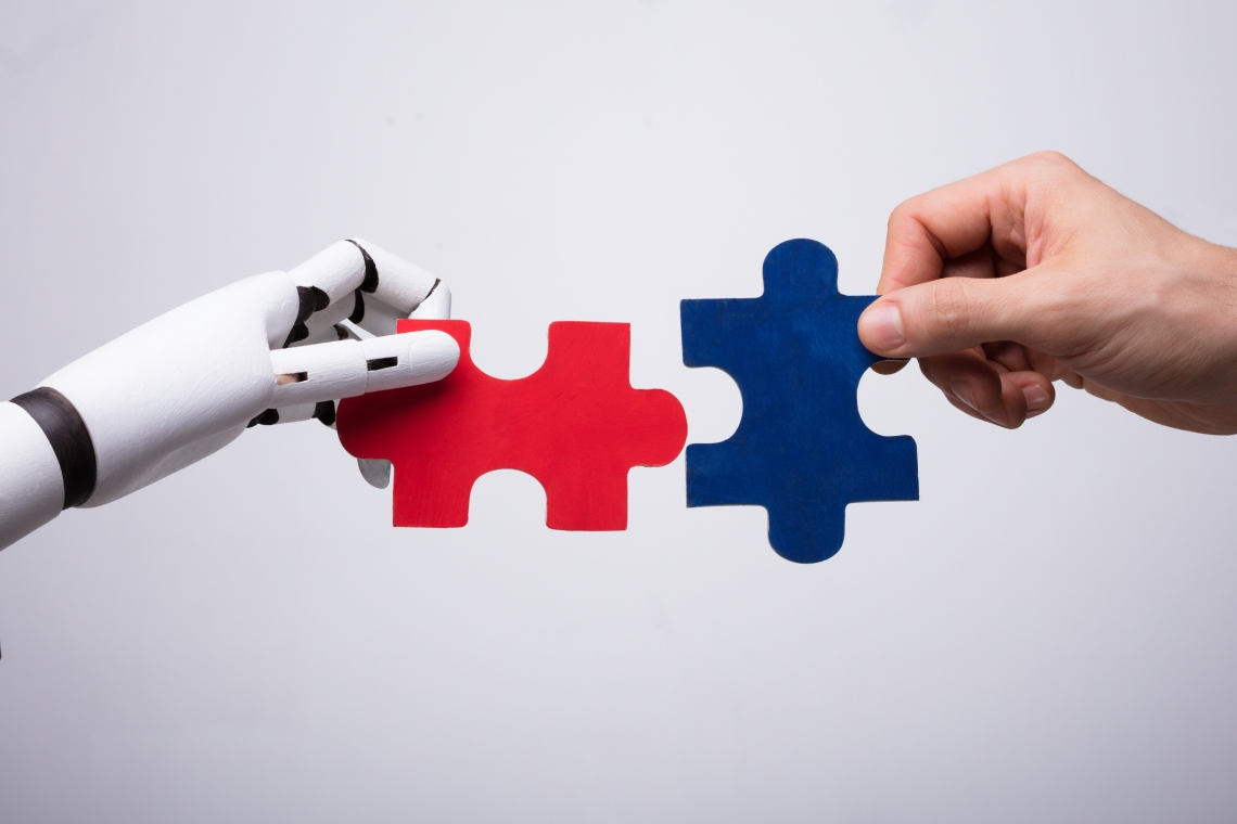 Robot And Human Hand Holding Jigsaw Puzzle